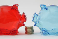 Two piggy banks face to face, with cion stack. Two piggy banks with differnt color standing face to face, with cion stack Stock Images