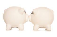 Two piggy banks kissing. Studio cutout Stock Photos