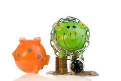 Two piggy banks with lock. An orange upside down piggy bank and a locked green piggy bank with coins Royalty Free Stock Photo