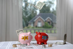 Two piggy banks and money. Two fat piggy banks and falling paper money mixed with coins Stock Photo
