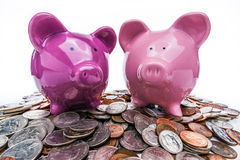 Two Piggy Banks. A picture of two piggy banks sitting on top of a pile of American coins Stock Photos