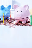 Two piggy banks on pile of coins. Two piggy banks standing on pile of coins behind colored pencils fence Stock Photo