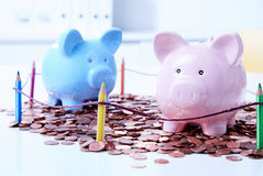 Two piggy banks standing among coins. Behind colored pencils fencing Royalty Free Stock Photography