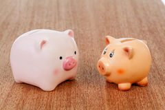 Two piggy banks on table. Pink and brown piggy banks on a wooden table Royalty Free Stock Image