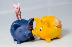 Happy piggy banks with money Stock Photo
