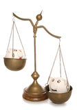Two piggy banks on weighing scales. Cutout Stock Images