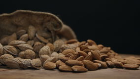 Two piles of almonds in shell and shelled on a wooden table isolated on black stock footage