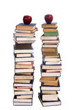 Two piles of books. Two tall stacks of books with an apple on each Stock Image