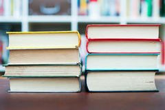 Two piles of books with library in background Royalty Free Stock Photo
