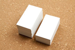Two piles of business cards on corkboard backgroun. Stock Image