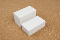Two piles of business cards on corkboard background. Royalty Free Stock Images