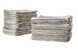 Two piles of newspapers. On a white background Stock Image