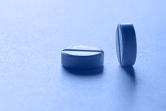 Two pills. Close view of two pills in blue light Royalty Free Stock Image