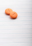 Two pills on lined paper Stock Image