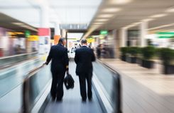 Two pilots. On a moving escalator Royalty Free Stock Images