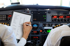 Two Pilots in aircraft with checklist Stock Photography
