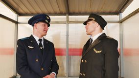 Two pilots discuss  occupation aviation  flight plane check  uniform. Two pilots discuss occupation aviation flight plane check uniform talk stock footage