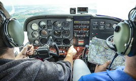 Two pilots flying. Single engine Cessna C172 aircraft by visual flight rules with visual flight map Royalty Free Stock Image