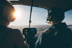 Two pilots in a helicopter while flying on a sunny day Stock Photos
