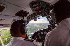 Two pilots landing a small aircraft to Nausori airport airstrip near Suva, Fiji, Melanesia, Oceania. Air travel in Fiji, cockpit. royalty free stock image