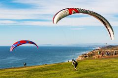 Two Pilots Launch Paragliders at Torrey Pines Gliderport. LA JOLLA, CALIFORNIA - FEBRUARY 17, 2018:  Two pilots launch paragliders at the Torrey Pines Gliderport Royalty Free Stock Photography