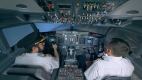 Two pilots turn the plane in a flight simulator. Pilots turn the plane to the right in a simulator stock video