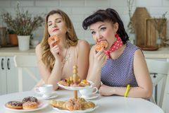 Two pin up girls emotionally eat a donut in the kitchen at the table Royalty Free Stock Image
