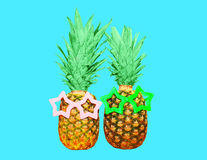 Two pineapple with sunglasses on blue background, ananas. Two pineapple with sunglasses on blue background, colorful ananas Stock Photo