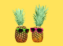 Two pineapple with sunglasses on yellow background, colorful ananas. Concept Royalty Free Stock Photo