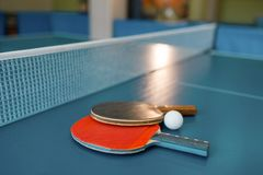 Two ping pong paddles on the table with net. Nobody, closeup view. Table-tennis club, tennis concept royalty free stock image