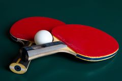 Two ping-pong rackets and a ball on a green table royalty free stock images