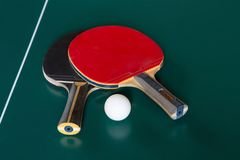 Two ping-pong rackets and a ball on a green table. Close-up royalty free stock photos