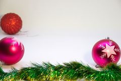 Two pink balls, one red ball,  Christmas decorations. Festive, Christmas card,two pink balls,one red ball in corner  and Christmas decorations on a white Royalty Free Stock Photography