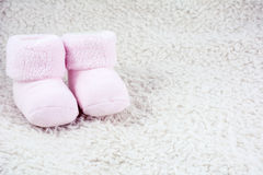 Two pink bootees for babies. On the white fur Royalty Free Stock Photography