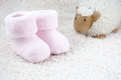 Two pink booties for babies with one toy sheep. On the white fur stock image