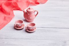 Two pink ceramic tea cups and a teapot on the table. Invitation card stock photo