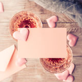 Two pink champagne glasses with blank paper toned card Royalty Free Stock Image