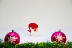 Two pink christmas balls,red hat toy Santa and Christmas decoration on a white background. Festive, Christmas card,pink balls,red hat toy Santa Claus and Royalty Free Stock Photo