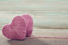 Two pink clews in shape of heart. On vintage wooden background Stock Photos