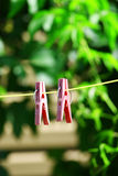 Two pink clothes pins. Two clothes pins on green background stock photo
