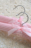 Two pink clothing hangers on crocheted background Stock Images