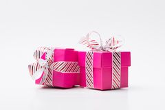 Two pink gift box tied with white red stripe ribbon. Two pink color gift boxes tied with white red stripe ribbon isolated on white background royalty free stock images