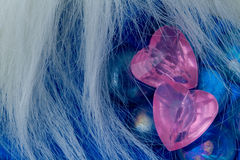 Two pink crystal heart shapes on blue glasses Stock Photography