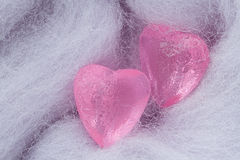 Two pink crystal heart shapes on woolen textile Royalty Free Stock Photography