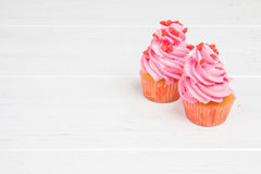 Two pink cupcakes on white wooden background. Valentine`s Day. Stock Photo