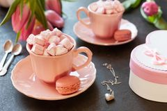 Two pink cups with pink heart shaped marshmallows with macaroons, pink tulips, gift box and silver heart shape pendant on chain. Romantic breakfast for two royalty free stock images