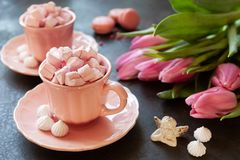 Two pink cups with pink heart shaped marshmallows, pink tulips, angel figurine and silver heart shape pendant on chain. Romantic. Breakfast for two. Close-up stock images