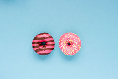 Two pink donuts on the blue table Stock Images
