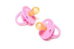 Two pink dummies or pacifiers. Isolated on white background stock photography