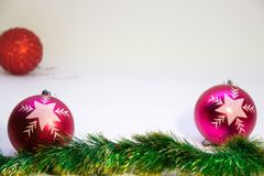 Two pink festive balls in focus with a red ball in the corner out of focus. Festive, Christmas card,two vertical pink balls, and Christmas decorations on a white Royalty Free Stock Photo